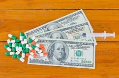 药片和注射器在一百美元在木背景 库存照片