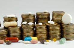 药片和硬币在白色 库存图片