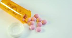 药片和药物转动 许多转动的药片特写镜头  溢出医疗药片的药瓶 处方瓶和 股票录像