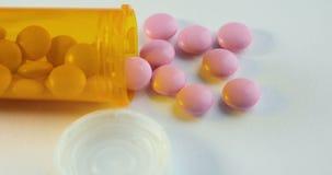 药片和药物转动 许多转动的药片特写镜头  溢出医疗药片的药瓶 处方瓶和 影视素材