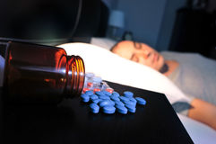 药片和年轻人在床上 免版税库存图片