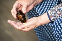 药片在一个老妇人特写镜头的手上 图库摄影