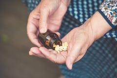 药片在一个老妇人特写镜头的手上 免版税库存照片