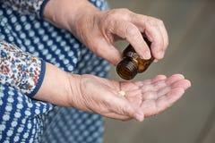 药片在一个老妇人特写镜头的手上 免版税库存图片