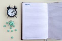 药片在日历和日志倾吐在一个玻璃杯子,药片外面准时驱散了,作为药片,写 r 免版税库存图片