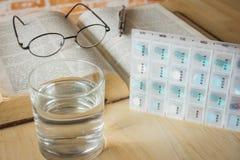 药片在星期装箱并且分离与医学和书的时间 免版税库存照片