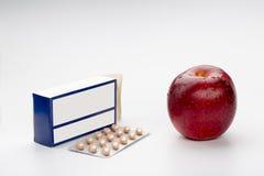 药片天线罩包装箱子和红色苹果 库存照片