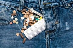 药片或医学片剂在近牛仔裤驱散了用拉锁拉上,牛仔布背景 有五颜六色的药片和水银温度表的邮编 图库摄影