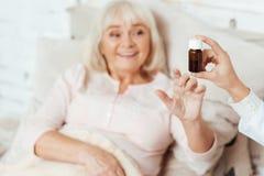 给药片的专业医生一个老妇人 免版税库存照片
