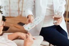给药片的宜人的有同情心的护士一名年长妇女 免版税库存照片