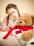 给药片的小女孩病的玩具熊 免版税图库摄影