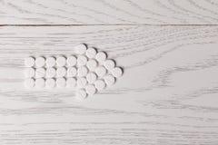 药片箭头在桌上的 免版税图库摄影