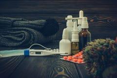 药片,滴鼻剂一种冷的治疗,流感流动在与一个电子温度计的桌上,定了调子图象 库存图片