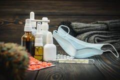 药片,滴鼻剂一种冷的治疗,流感流动在与温度计的桌上 免版税库存图片