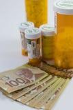 药片bottls和加拿大金钱 免版税库存图片