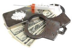 药物、注射器有血液的,手铐和金钱在白色 免版税库存图片