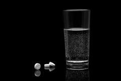 药物和一块玻璃用水在黑背景 库存图片
