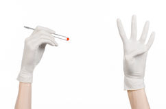 药理和医疗题材:在拿着有红色药片胶囊的一副白色手套的医生的手镊子隔绝在白色背景 免版税图库摄影