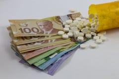 药瓶被打翻的和加拿大金钱 库存图片