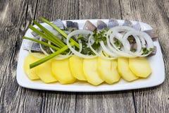 荷兰全国开胃菜,鲱鱼用葱 冰岛鲱鱼鲜美片断用煮沸的土豆和葱在板材 库存照片
