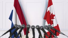 荷兰和加拿大的旗子在国际会议或交涉新闻招待会 股票视频