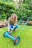 年轻荷兰妇女reparing的割草机在庭院里 免版税库存图片