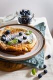 荷兰婴孩薄煎饼服务用新鲜的莓果和薄菏 关闭 早餐,餐馆,菜单概念 免版税库存照片