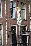 荷兰房子前面-小船通过运河在阿姆斯特丹,荷兰,荷兰Grachtengordel西部地区游览  免版税库存照片