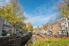 荷兰扁圆形干酪,荷兰:荷兰扁圆形干酪传统荷兰运河房子与树的在秋天颜色 免版税图库摄影