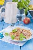 荷兰薄煎饼用早餐明亮的颜色的火腿,蓝色背景 鲜美和热量 一杯水和一个水罐酒 自由 免版税库存照片