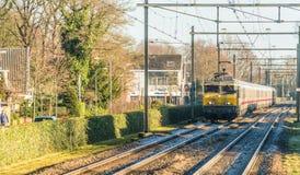 荷兰语训练有通过村庄的germand无盖货车的机车在冬天期间 图库摄影
