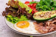 荷包蛋、烟肉、鲕梨、芝麻菜和草莓 Keto早餐 库存照片