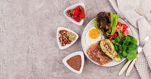 荷包蛋、烟肉、鲕梨、芝麻菜和草莓 Keto早餐 库存图片