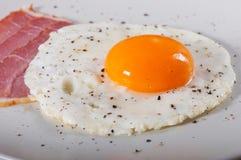 荷包蛋和烟肉在一块轻的板材 免版税库存照片