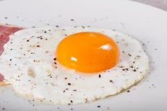 荷包蛋和烟肉在一块轻的板材 免版税库存图片