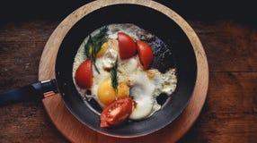 荷包蛋用在一个土气样式的一个平底锅和莳萝油煎的蕃茄 古色古香的木窗口基石立场 免版税库存照片