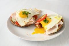 荷包蛋用在全麦面包卷的连续卵黄质用蕃茄、黄瓜和煮熟的火腿,在白色的健康热诚的早餐 图库摄影