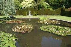 荷花池塘和一个雕象在修剪的花园从事园艺 库存照片