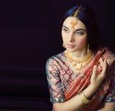 莎丽服的秀丽甜真正的印度女孩微笑在黑背景,首饰发光的特写镜头的 库存图片
