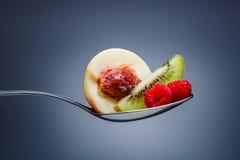 莓、桃子和猕猴桃在弯曲的匙子 免版税库存图片
