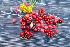 莓、红浆果樱桃和葡萄在一张木桌上的 图库摄影
