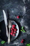 莓、葡萄酒利器和黑色的盘子 库存照片