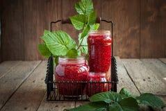 莓叶子和果酱在瓶子在木桌上 库存图片