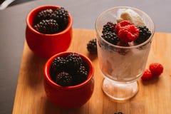黑莓在一块杯子和玻璃的冰淇凌在木板背景弄脏了绿色 库存图片