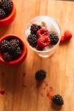 黑莓在一块杯子和玻璃的冰淇凌在木板背景弄脏了绿色 库存照片