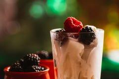黑莓在一块杯子和玻璃的冰淇凌在木板背景弄脏了绿色 免版税图库摄影