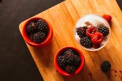 黑莓在一块杯子和玻璃的冰淇凌在木板背景弄脏了绿色 免版税库存照片