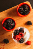 黑莓在一块杯子和玻璃的冰淇凌在木板背景弄脏了绿色 免版税库存图片