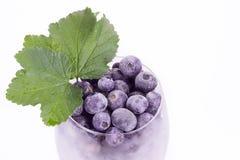 莓果品种在玻璃的与叶子 免版税库存图片