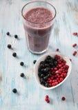 莓果圆滑的人用杏仁牛奶、蔓越桔、aronia和黑古芝 免版税库存图片